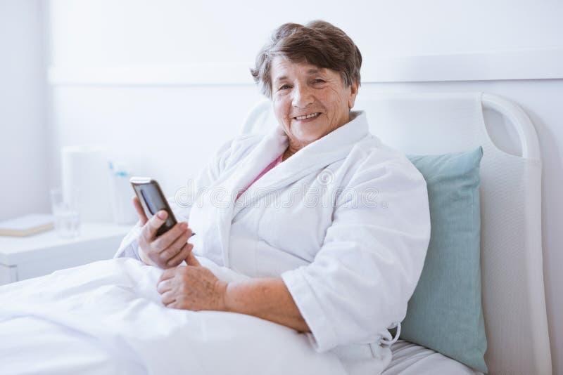 Smiling senior lady holding mobile phone while sitting in hospital bed. Smiling senior lady holding mobile phone while sitting in bed royalty free stock photo