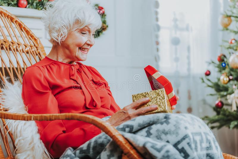 Happy old woman is holding gift box stock images