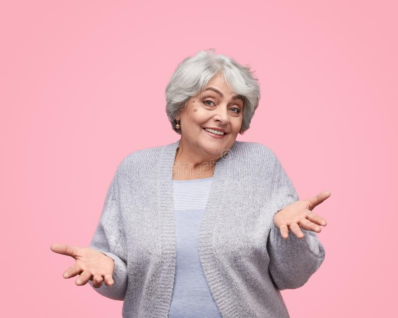 Smiling senior lady shrugging shoulders stock photography