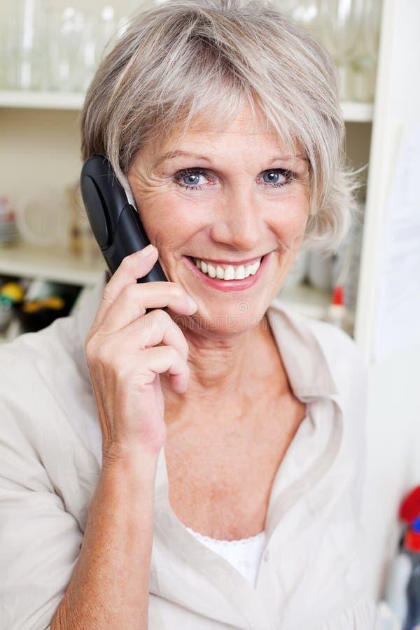 Smiling senior lady talking on a telephone royalty free stock photo