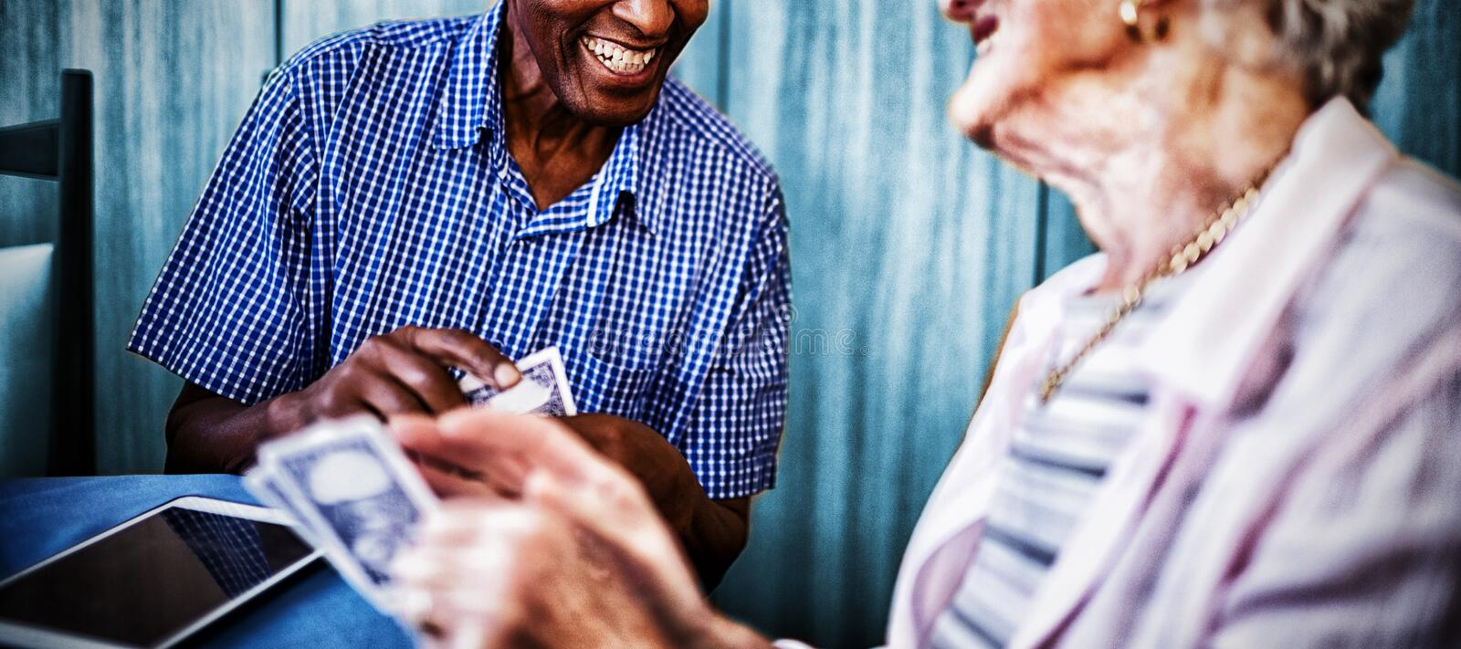 Smiling senior male and female friends playing cards stock images