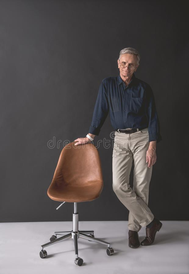 Smiling senior male standing near seat stock photography