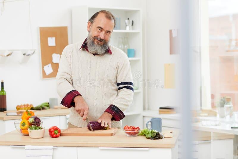 Smiling Senior Man Cooking in Kitchen royalty free stock images