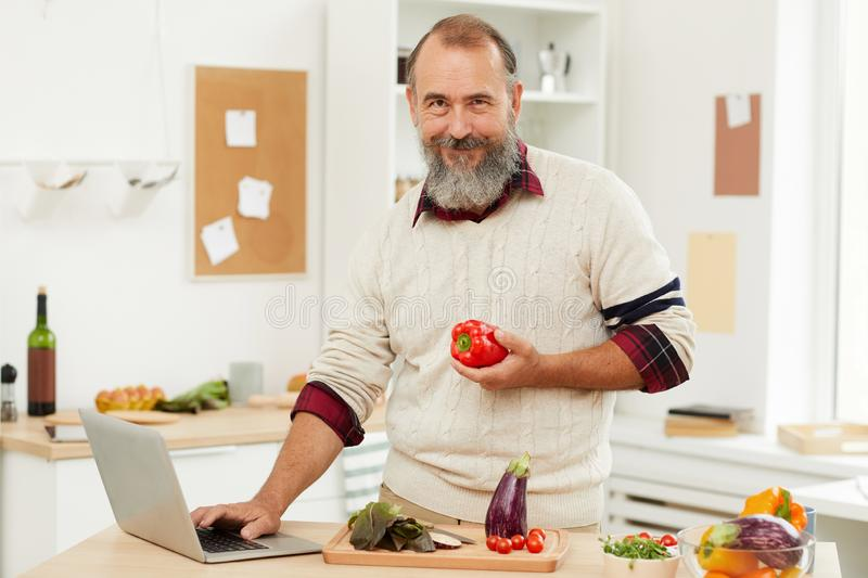 Smiling Senior Man Cooking by Online Tutorial stock photography