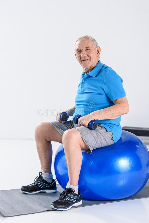 smiling senior man with dumbbells sitting on fitness ball royalty free stock photos