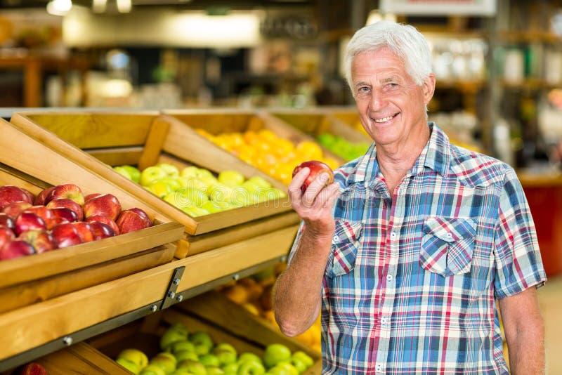 Smiling senior man holding apple royalty free stock photo