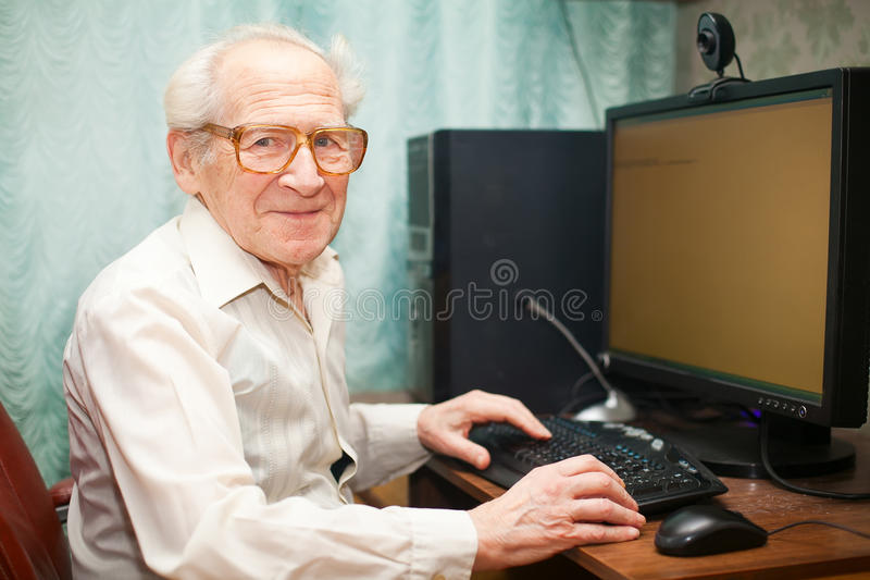 Smiling Senior Man Near Computer. Smiling happy old man sitting near computer and holding mouse stock photography