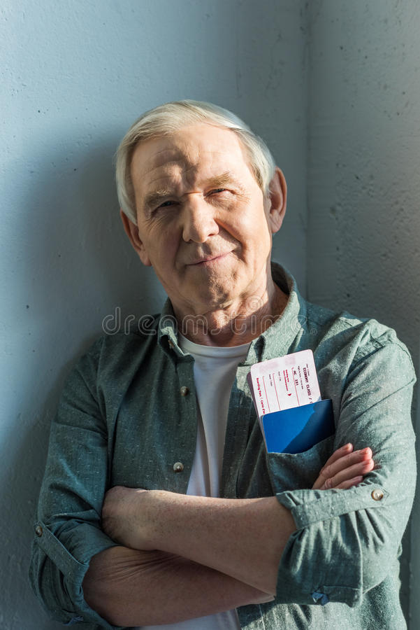Smiling senior man with passports and tickets in pocket, traveling concept royalty free stock photography