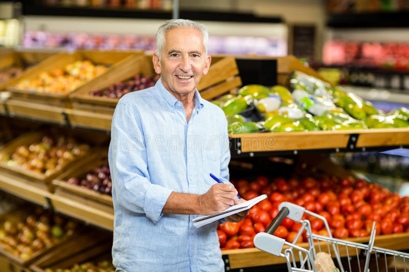 Smiling senior man with shopping list stock photography