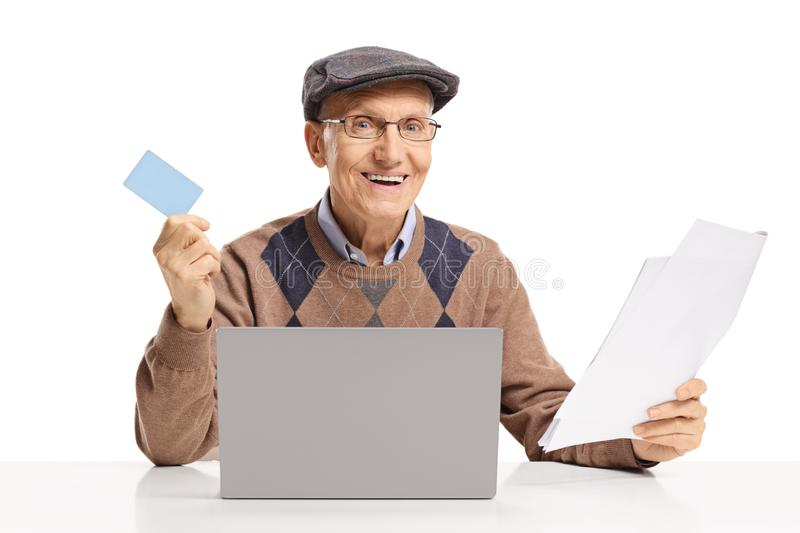 Smiling senior man sitting in fron of a laptop computer and holding papers and a credit card. Isolated on white background stock photography