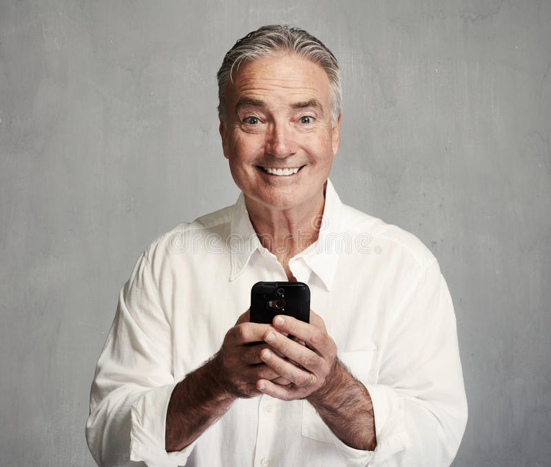 Smiling senior man with smartphone. Smiling senior man text message with smartphone stock photo