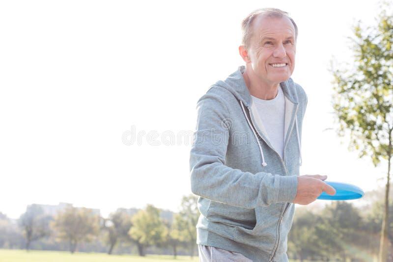 Smiling senior man throwing disc in park stock images