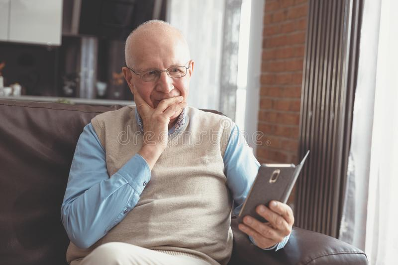 Smiling senior man using a smartphone stock photography