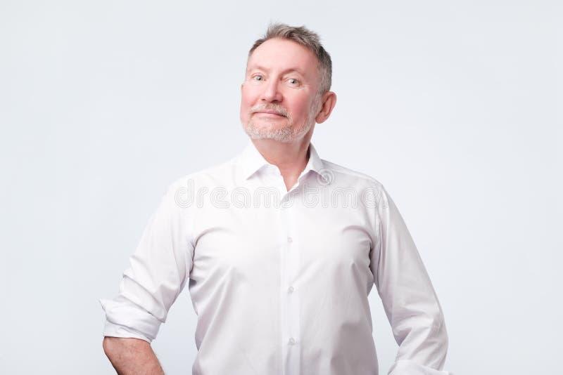 Smiling senior man in white shirt standing and smiling at camera feeling good stock photo