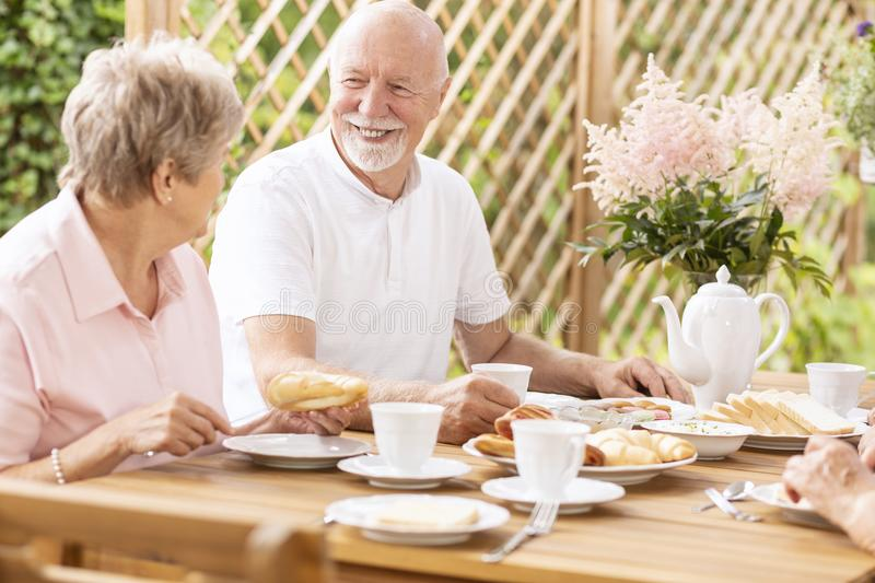 Smiling senior man eating breakfast with elderly woman on the te royalty free stock photos