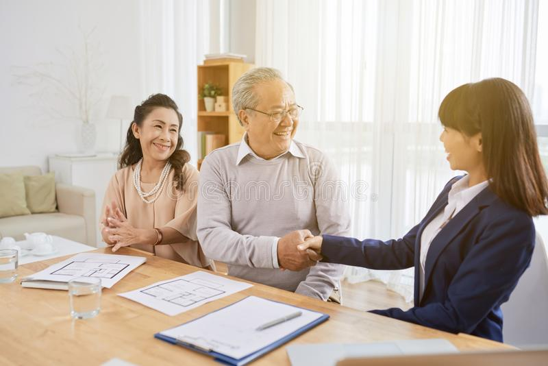 Signing Real Estate Purchase Agreement. Smiling senior men shaking hand of pretty young realtor after signing real estate purchase agreement, interior of cozy royalty free stock image