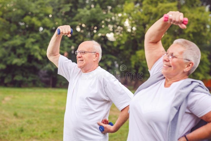 Senior man and woman are outdoors in a park exercise with dumbbells and having fun together. Smiling senior men and women are outdoors in a park exercise with stock photography