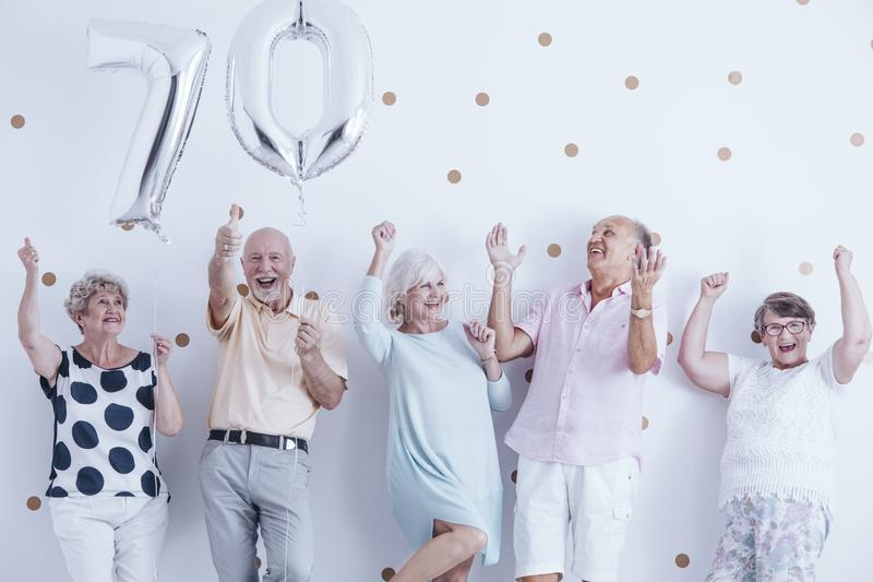 Smiling senior people celebrating with silver balloons royalty free stock photos