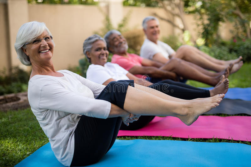 Smiling senior people exercising with feet up stock photography