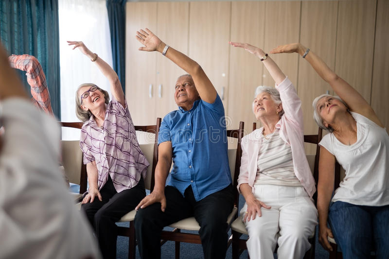 Smiling senior people stretching with female doctor stock photo