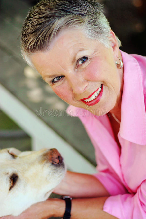 Smiling Senior. Photo of an attractive senior lady smiling and enjoying life with her dog