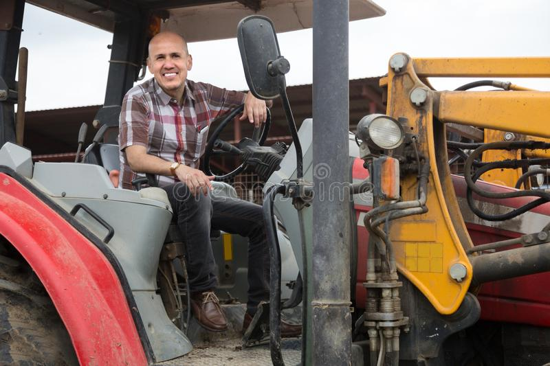 Senior positive operating modern tractor in livestock farm. Smiling Senior positive operating modern tractor in livestock farm royalty free stock images