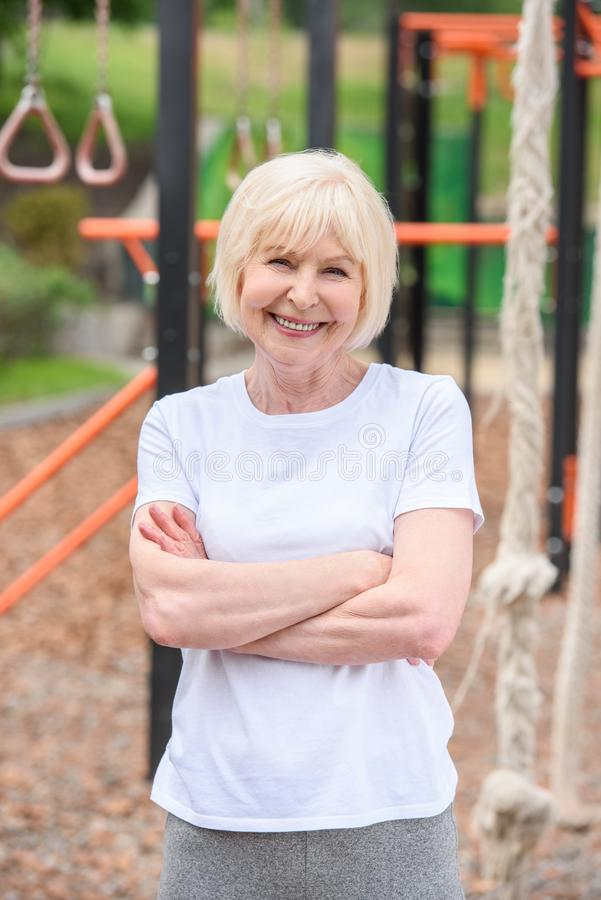 smiling senior sportswoman with crossed arms standing stock images