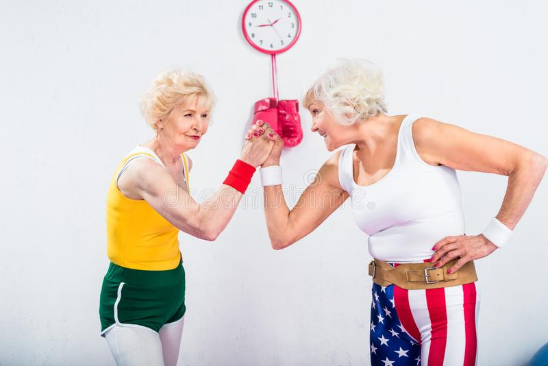 Smiling senior sportswomen wrestling and looking at each other. In gym stock photography