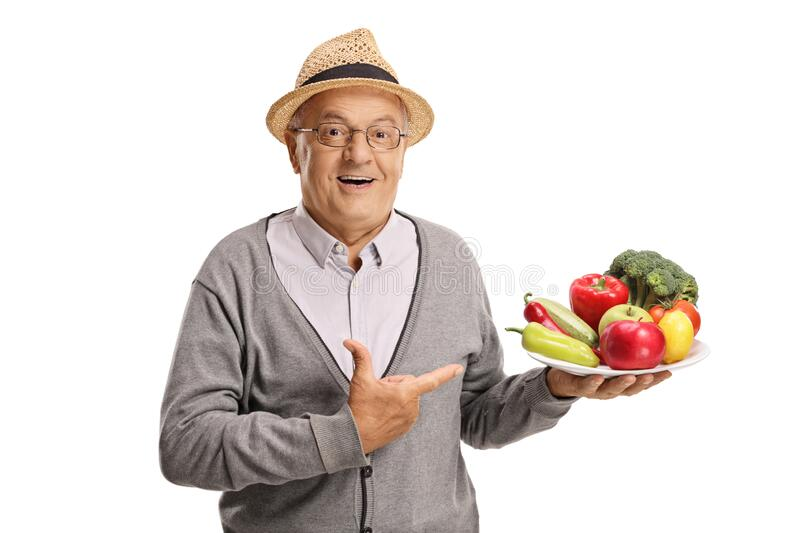Smiling senior vegan holding a plate of fruits and vegetables and pointing stock photos
