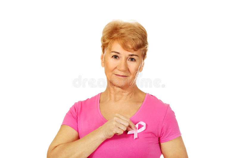 Smiling senior woman with breast cancer awareness ribbon stock image
