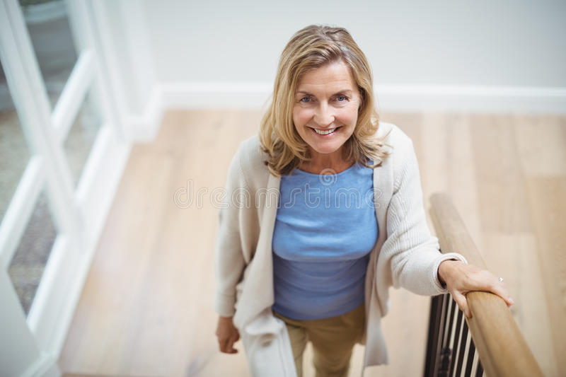 Smiling senior woman climbing upstairs at home stock photos
