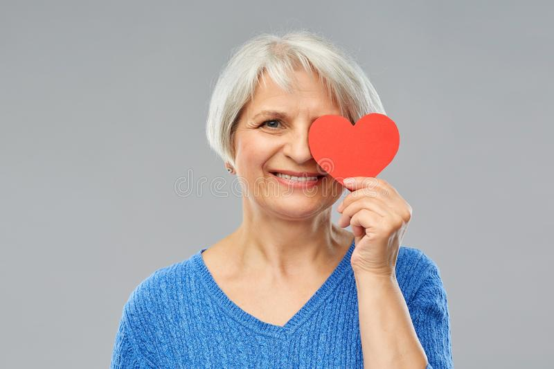 Smiling senior woman covering eye with red heart. Valentine`s day, summer and old people concept - portrait of smiling senior woman covering one eye with red stock photos
