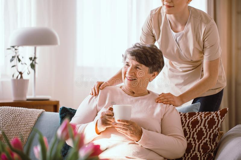 Smiling senior woman drinking tea with her caregiver standing behind her royalty free stock photo