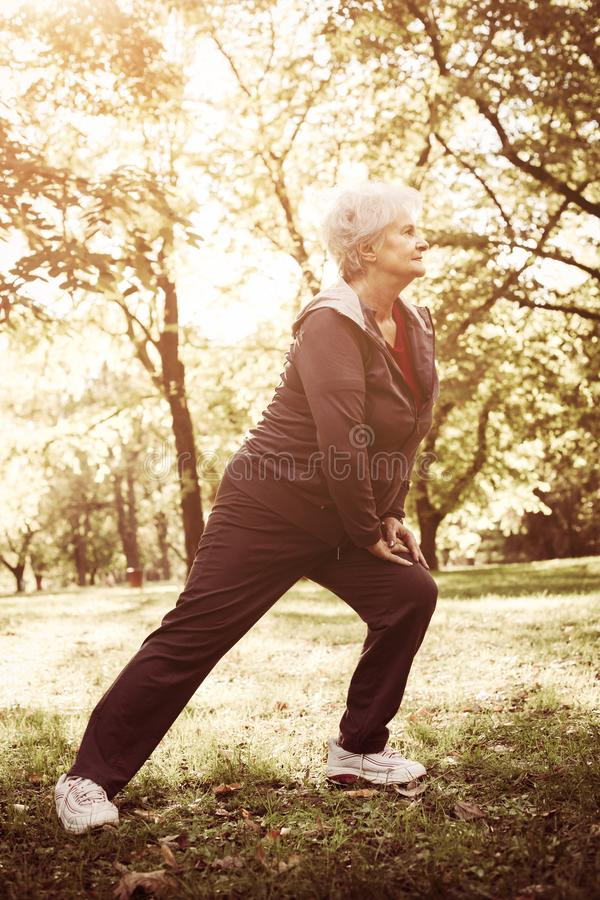 Senior woman exercising alone in forest and looking away royalty free stock images