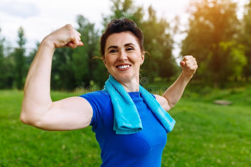 Smiling Senior woman flexing muscles outdoor in park. Elderly female showing biceps. Heathy life style concept stock photos