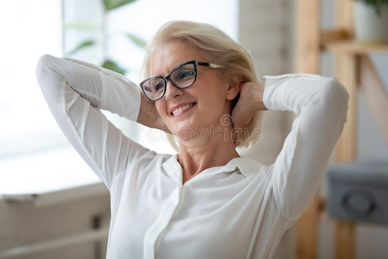 Happy senior woman relax with hands over head stock image