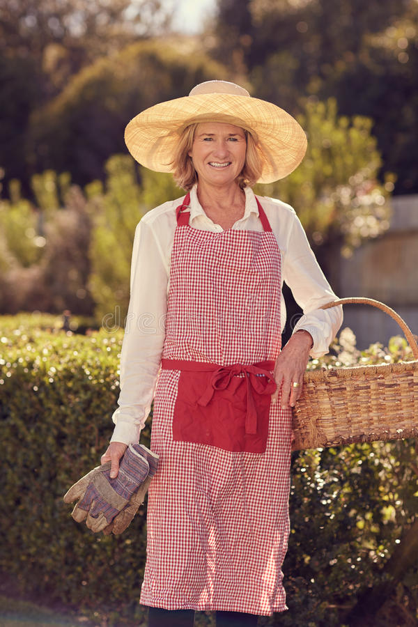 Smiling senior woman with hat, apron, gardening gloves and baske royalty free stock photography