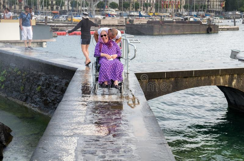 Smiling senior woman with his son, sitting on wheelchair near Jet d'Eau -  large fountain in Geneva, Switzerland. GENEVA, SWITZERLAND - JUNE 24, 2017: Smiling stock photography