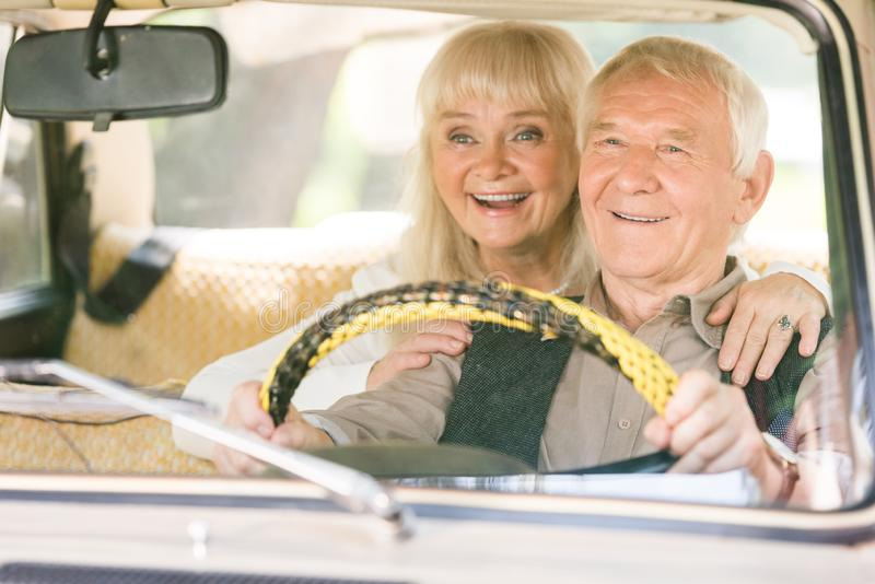 Smiling senior woman hugging man while he driving. Retro car royalty free stock photos
