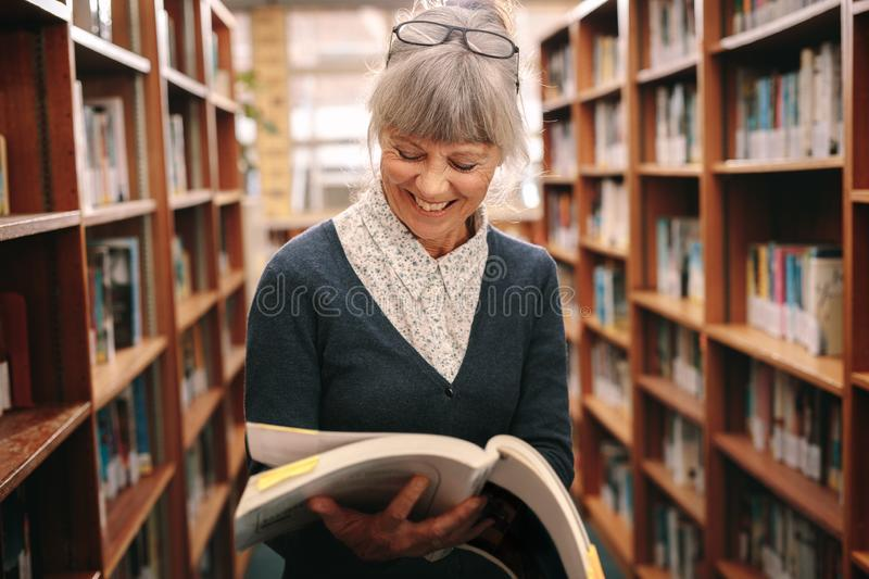 Smiling senior woman looking at a book standing in a library stock images