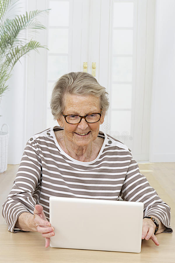 Smiling Senior Woman Looking At Her Computer Stock Photo