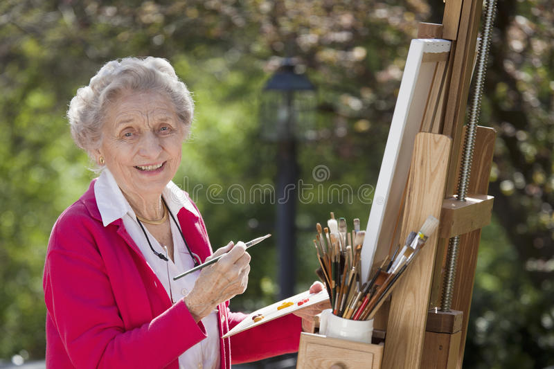 Smiling Senior Woman Painting stock photo