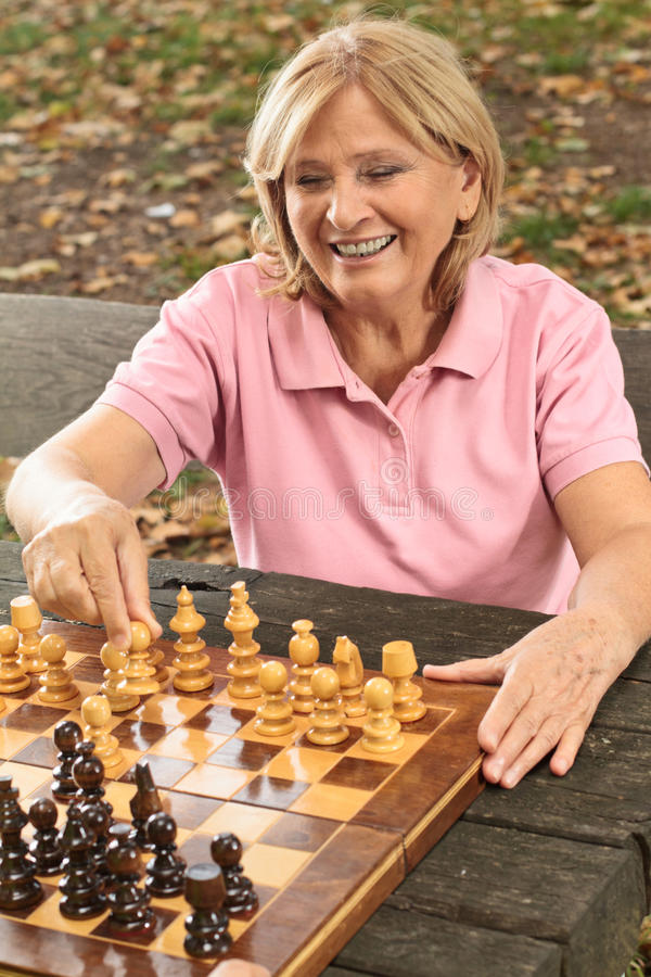 Smiling senior woman playing chess royalty free stock photography