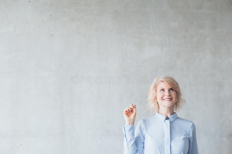 Smiling senior woman pointing up advertisement royalty free stock photography