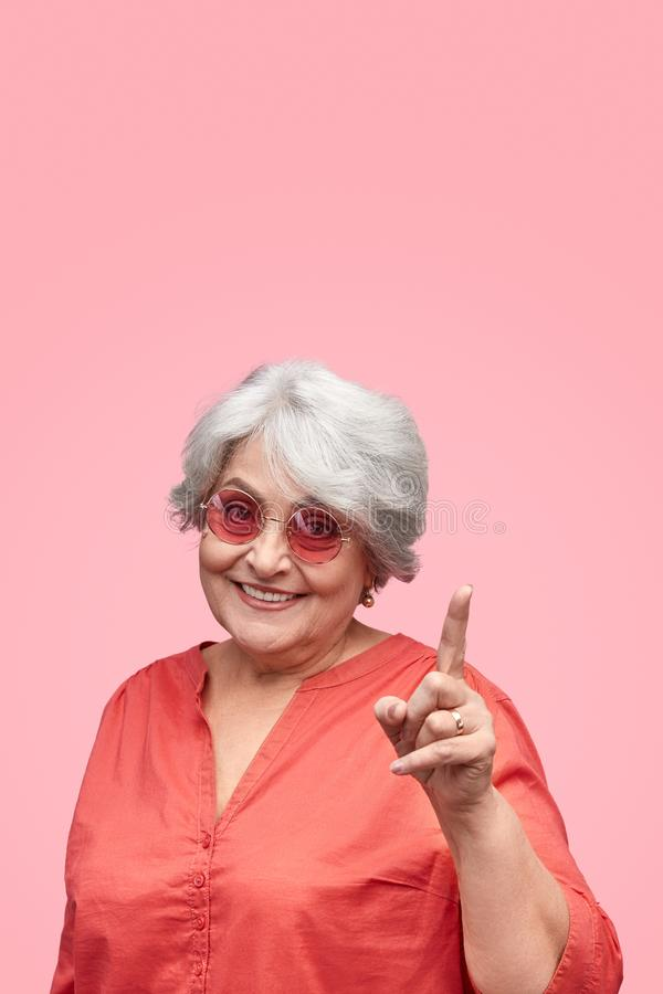 Smiling senior woman pointing up stock images