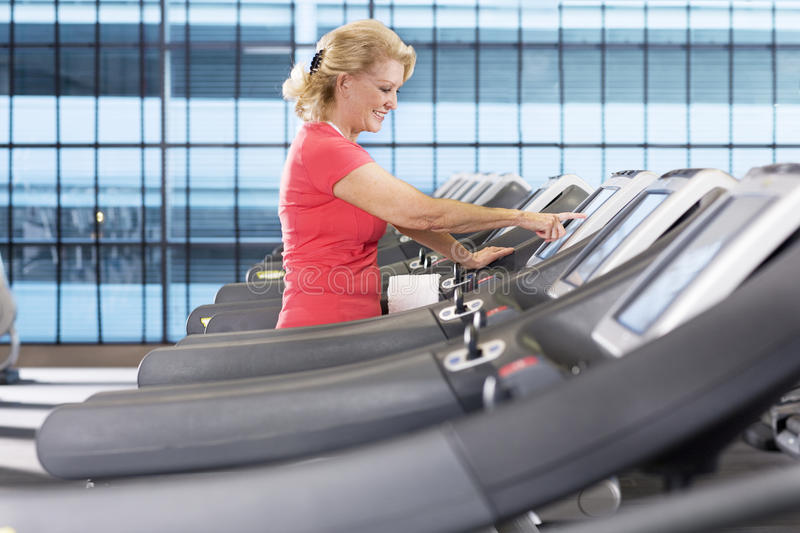 Smiling senior woman programming treadmill in health club royalty free stock photography