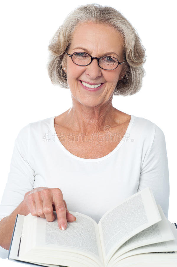 Smiling senior woman reading a book stock images