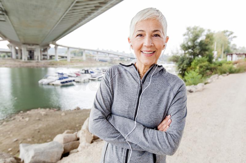 Smiling Senior Woman Relax Listening Music With Earphones After Running royalty free stock photos