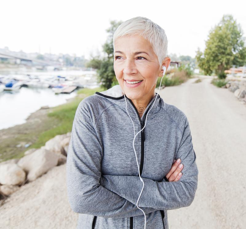 Smiling Senior Woman Relax Listening Music With Earphones After Running royalty free stock photo