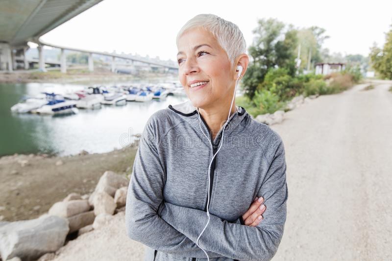 Smiling Senior Woman Relax Listening Music With Earphones After Running stock photo
